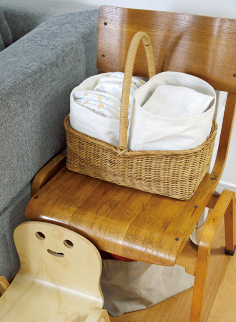 画像: おむつ替えの定位置はソファ。おむつはかごに入れてすぐそばに置いている