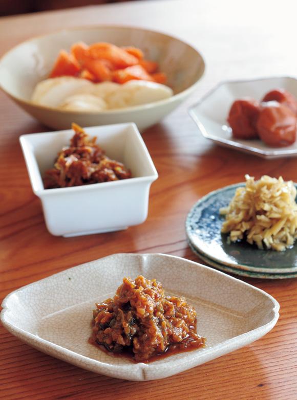 画像: 梅干しから時計まわりに、しょうがのナンプラー煮、ピーマン味噌、しょうがのつくだ煮、ぬか漬け。ピーマン味噌は、しょうゆを数時間ふくませた米麹に炒めたピーマンとえのきを炊き合わせた保存食
