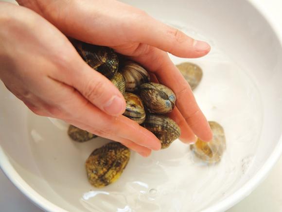画像: ボウルなどに入れ、流水の下で貝同士をこすり合わせるように洗う