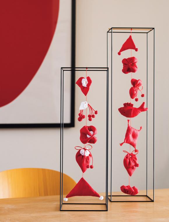 画像: 赤と白に色を絞り、シンプルなオリジナルの吊るし雛をつくった。鉄製のキューブフレームは鍛鉄(たんてつ)作家の渡辺薫さんにつくってもらった