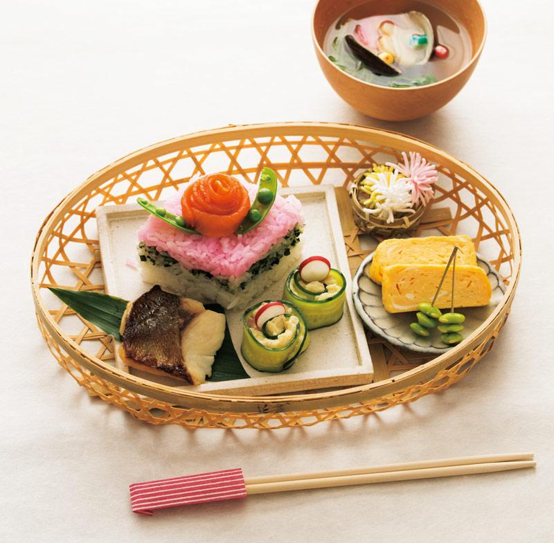 画像: ひし形のお寿司は、7cmくらいの高さに切った牛乳パックを型として使用。ピンクはでんぶ、緑はワカメのふりかけを混ぜて。花形のつけ合わせは「開花宣言」というそう麺を揚げたもの。ポテトサラダも薄く切ったきゅうりで巻き、ラディッシュを添えれば、よそいきに