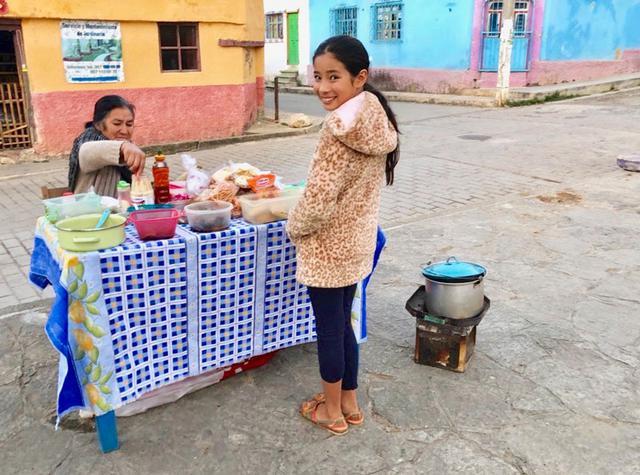 """画像: 旅も終盤のある日の夕方、レナちゃんに誘われて行った、""""行きつけの""""屋台。小さなテーブルには、素朴な手作りのおやつがたくさん。こんな買い食いができるなんて、なんて幸せな子ども時代でしょう。ご婦人が味見させてくださった甘く煮たパン、やさしい甘さでとてもおいしかった"""