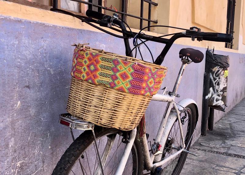 画像: 道端で見つけて、思わず釘付けになった自転車がこちら。サンクリ名物?の竹かごに、色鮮やかなマクラメ編みの飾りが巻かれた、なんともこの土地らしいデコレーション! 拍手を送りたい、素敵な手仕事です