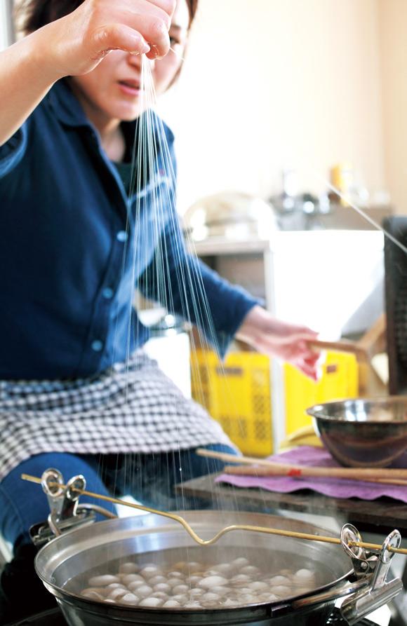 画像: 80〜100匹の繭を鍋で煮るうちに、糸の先端が自然と上を向く。菜箸で頭をなでてそろえ、いっせいに糸を引いて合わせ、一本の糸にしていく。最初に出るごつごつした部分「きびそ」は捨てる。お湯の温度は80℃だが、素手で作業