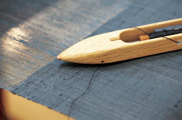 画像: シャトル(杼)を使って、緯糸を経糸に通していく。これは男性用の着尺。7〜10日で完成する