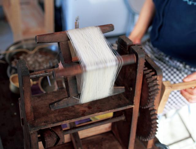 画像: 座繰り機と呼ばれる機械のハンドルを回しながら、引いた糸を巻き取っていく。一回で約1kmの糸をつくれる