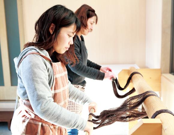 画像: 染色した糸に糊づけをする北村さん(奥)と南さん。ムラなくつけたあと、しぼって余分な糊を落とし、糸を振って解きほぐす