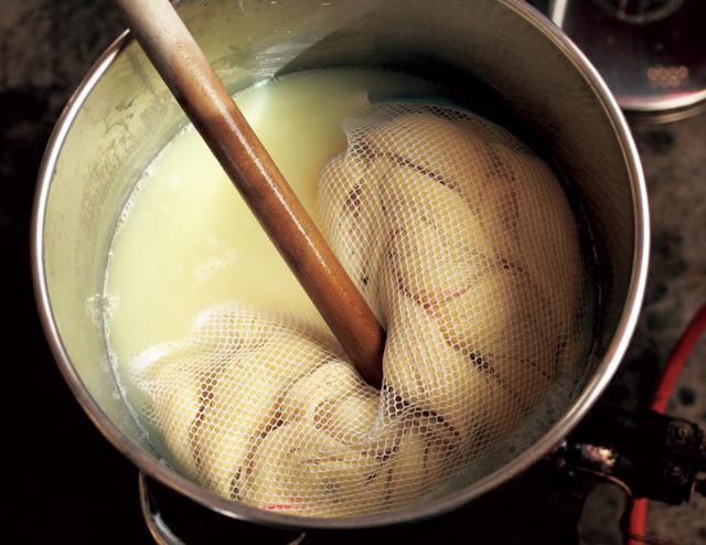 画像: 引き終わった糸から不純物を取り除く「精練」。お湯の色の変化や手の感触を確認しながら、適度にかき混ぜる