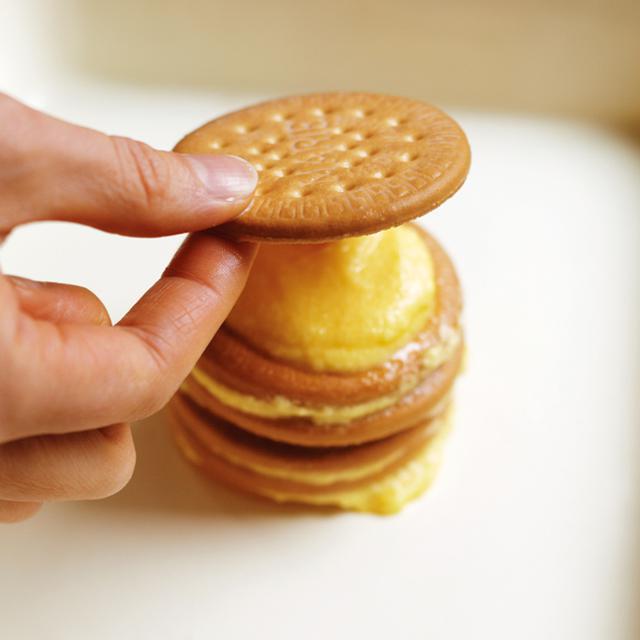 画像: 牛乳にひたしたビスケットの片面にクリームをぬり、もう1枚のせる。これを繰り返す