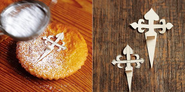 画像: サンティアゴの十字架の型紙は少し厚めの紙を使い、ケーキの大きさに合わせてつくっておく。粗熱をとったケーキに型紙を置いて粉砂糖をたっぷりとふりかけ、静かに型紙を取る