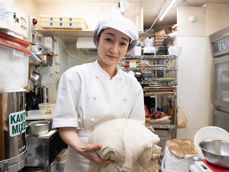 画像: オープン当初から石井さんの片腕として働くスタッフの弥生さん。日々変わる酵母の状態を見極めながら、毎日同じ味になるように焼き上げる