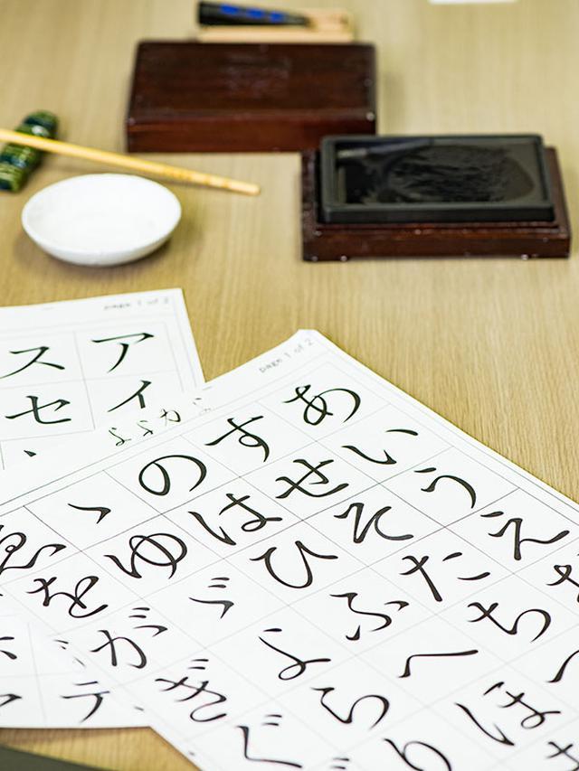 画像: パソコンも使うものの、手書き作業もしながらデザイン。極細の筆で細かい部分を修正
