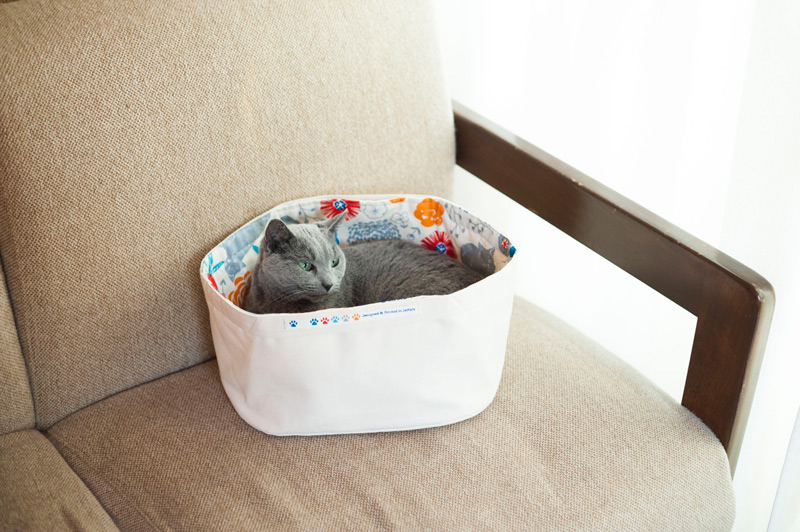 画像: 冒頭の写真で紹介した子どものおもちゃ入れをねこベッドに。ふんわりとした感触で持ち手に手足を引っ掛けにくいから、こんな使い方もおすすめ。表布は適度な張りがあるオックス、裏布はねこモチーフの柄を選んでキュートに。