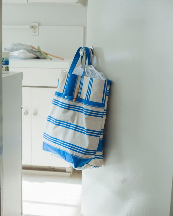 画像: 洗濯物をすっきりまとめられる縦型のランドリーバッグは、切り替え線につくったポケットに洗剤や洗濯ばさみを。口には市販の洗濯ネットを縫いつけ、中身の飛び出し防止に。巾着型にアレンジせず、元々ついているファスナーを生かしても。畳めるから長期旅行にも活躍。