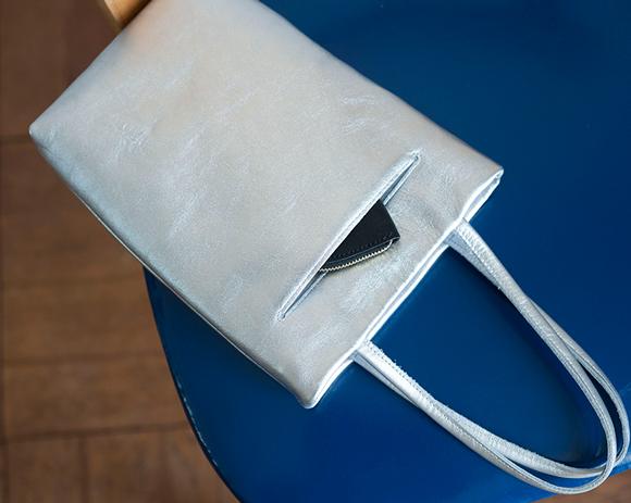 画像: 落ち着いた輝きを放つシルバーのラムレザーからイメージを膨らませた、アクセサリー感覚で使えるスリムバッグ。裁ち端の始末がいらない革の特性を生かしてポケットは切り込みを入れ、ナイロン地の袋布とミシンで縫い合わせ。