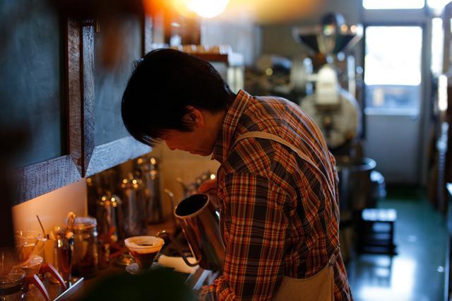 画像: カフェセラード店主・大竹謙志郎さん。常時数十種類を揃えるコーヒー豆はすべて、店舗奥の焙煎機で大竹さんが自ら焙煎。豆のまま販売のほか、ドリッパーの種類に合わせた挽き方の調整にも応じてくださいます(撮影:佐々木健太)