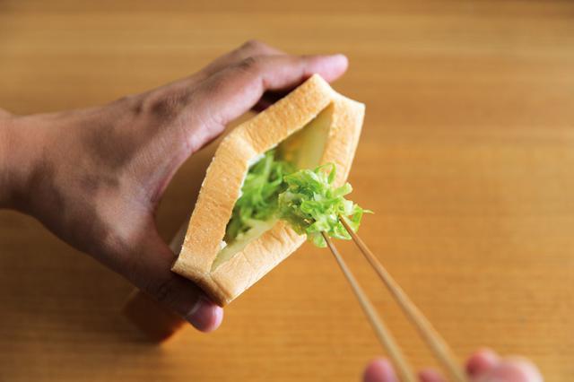 画像: 4枚切り食パンの脇から切込みを入れてポケット状に。そのポケットに、味付けしたせん切りキャベツを、詰めている。