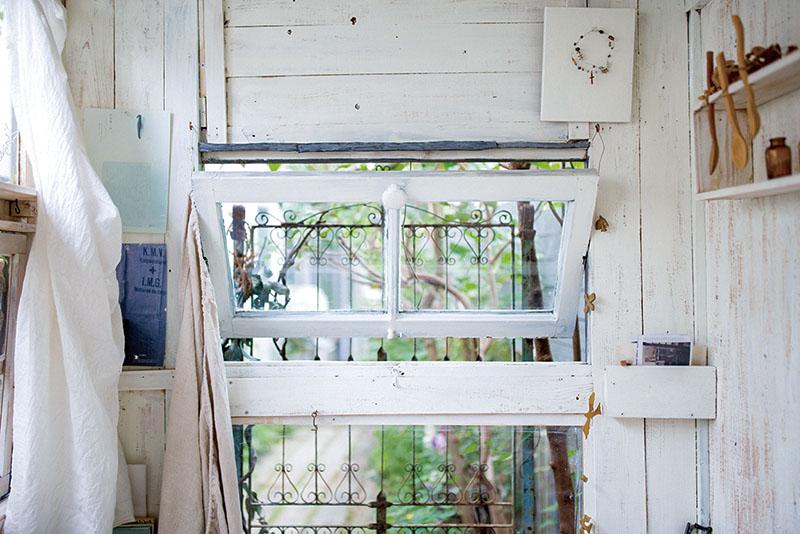 画像: 入って左手、奥の路地を見通す側には、回転式のガラス窓を設けた。友人づてに譲り受けていたものを取り付けた