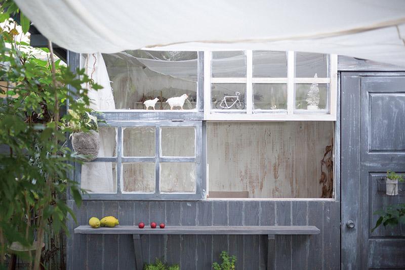 画像: 小屋正面の外壁には、幅が広く奥行きの小さな棚がしつらえられ、上部は柔かな布を渡して覆うこともできる