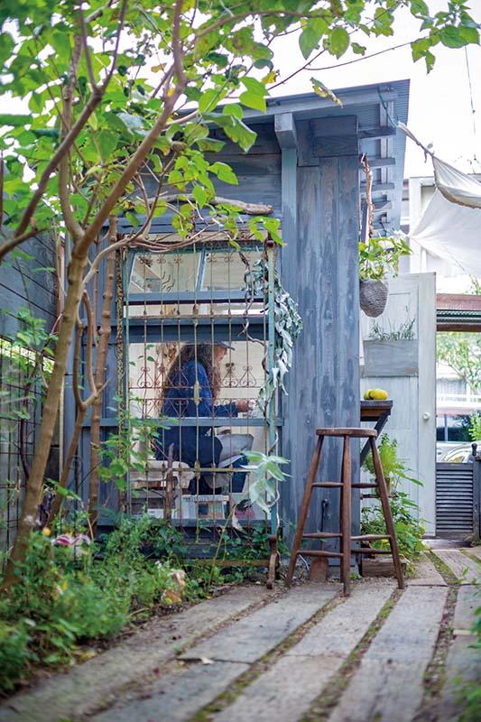 画像: 母屋の脇の「植物が再生する」という小径から、小屋の側面を見る。アンティークのフェンスやスツールも、緑とともに小屋に馴染んでいる