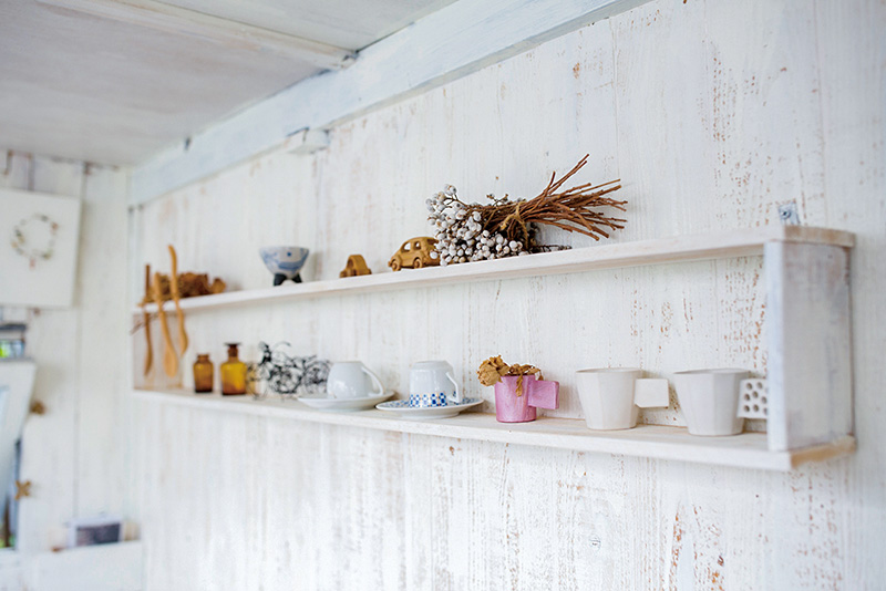 画像: 入って正面の壁、ベンチシートの上に設けられた棚には、小屋で使うお気に入りのカップのほか、手づくりの小物が並べられている