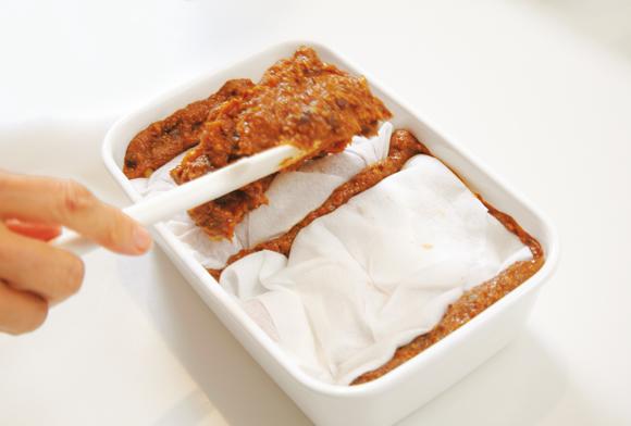画像: 上部の味噌を1/3くらい取り除き、ペーパータオルに包んだ豚肉をのせ、味噌をかぶせる
