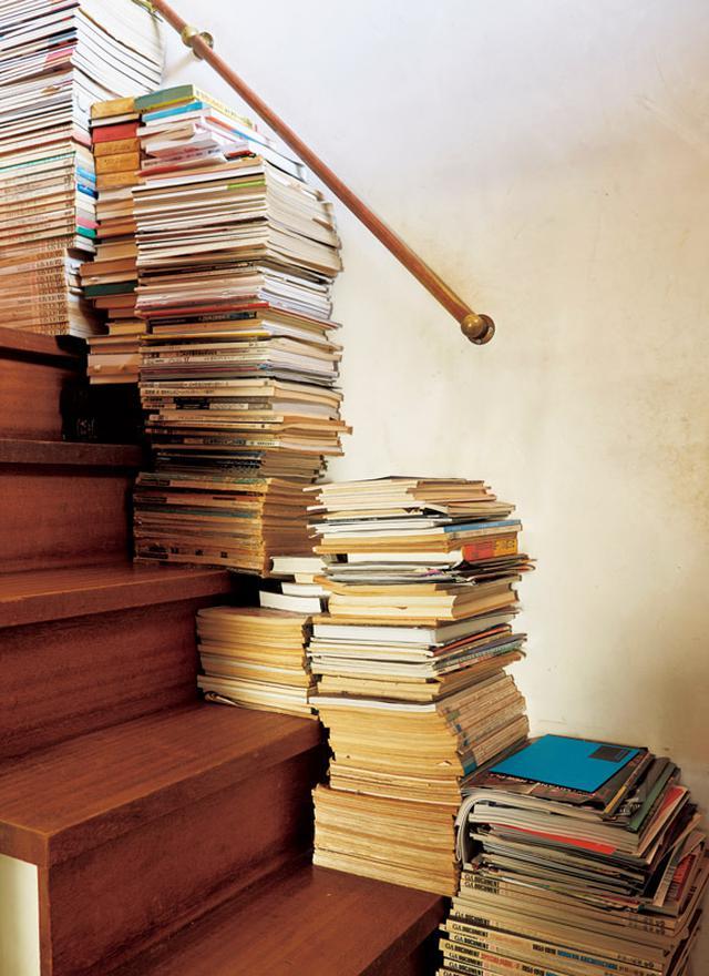 画像: 階段の幅を利用しない手はない。たくさんある蔵書は、家のあちこちに積まれている