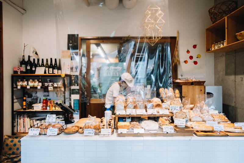 画像: カウンターの上に、ハード系パンから総菜パン、甘いパン、焼き菓子などが所狭しと並ぶ