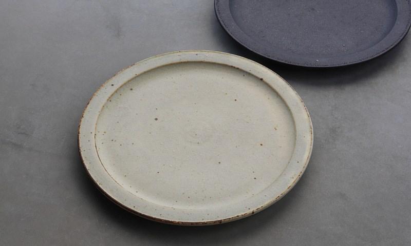 画像: ざらっとした土の風合いが生きた「土化粧リム皿」。手前がベージュで奥が黒。和も洋もどんなおかずも受けとめてくれる