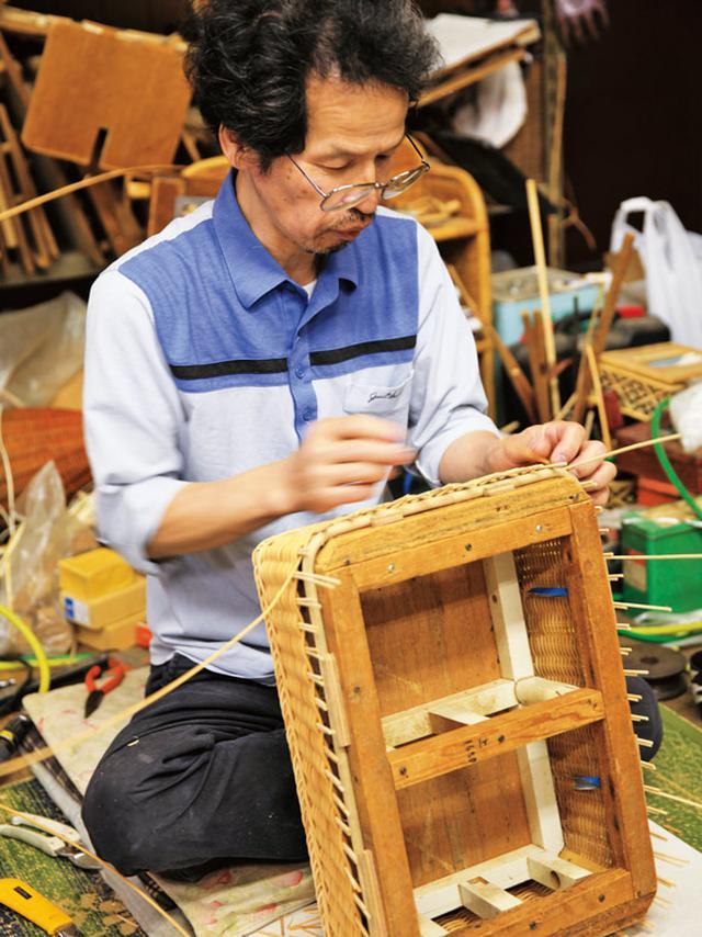 画像: 脱衣かごの上の部分を編む三男の利蔵さん。オーダーごとに3人の役割分担は変わる