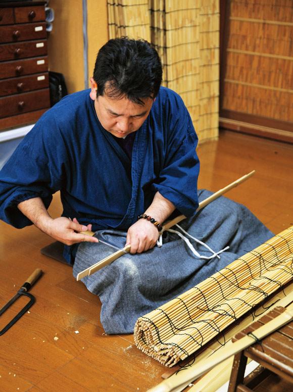画像: 編み上がったすだれの上下に竹を付けて仕上げるのは、五代目を継ぐ予定の息子さんが担当