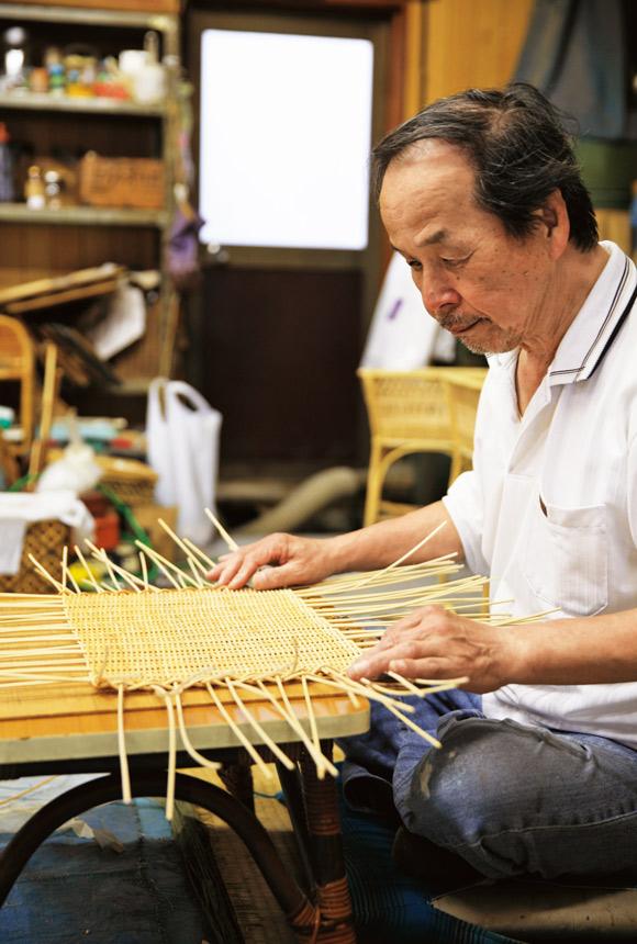 画像: 底の部分から脱衣かごを編みはじめる市村重治さん。50年以上のキャリアをもつ。籐は水分をふくませて、柔らかくしながら制作する