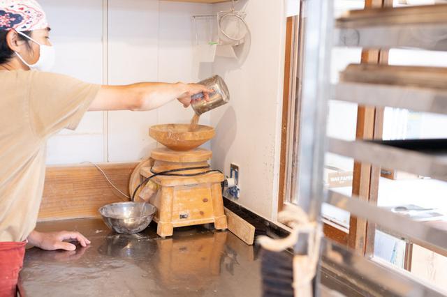 画像: 厨房にある小ぢんまりとした電動石臼。木製の台で、見た目も愛らしい