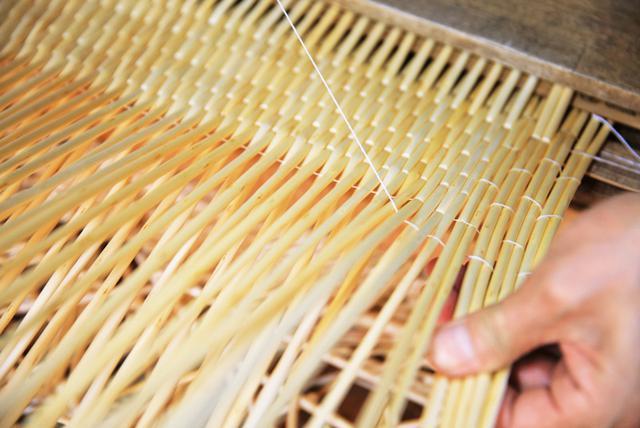 画像: 柳のしなりを利用して、間に麻糸を通し、固く編み締めていくのが杞柳細工の特徴。中央から外側に向かって編み、板状に仕立てていく