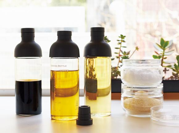 画像: 調味料は、保存容器に移し替えて保存するとよい。容器の大きさをそろえると保存がしやすい。松田さんは、ハリオのクッキングボトル(左)と、セラーメイトのチャーミークリア(右)を愛用