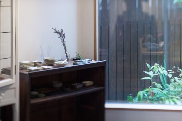 画像: 店内にある古家具はどれも、小池さん夫妻がご自宅で使っていたもの。窓からは山里をイメージしたという植栽が顔を覗かせ、心地いい空間に
