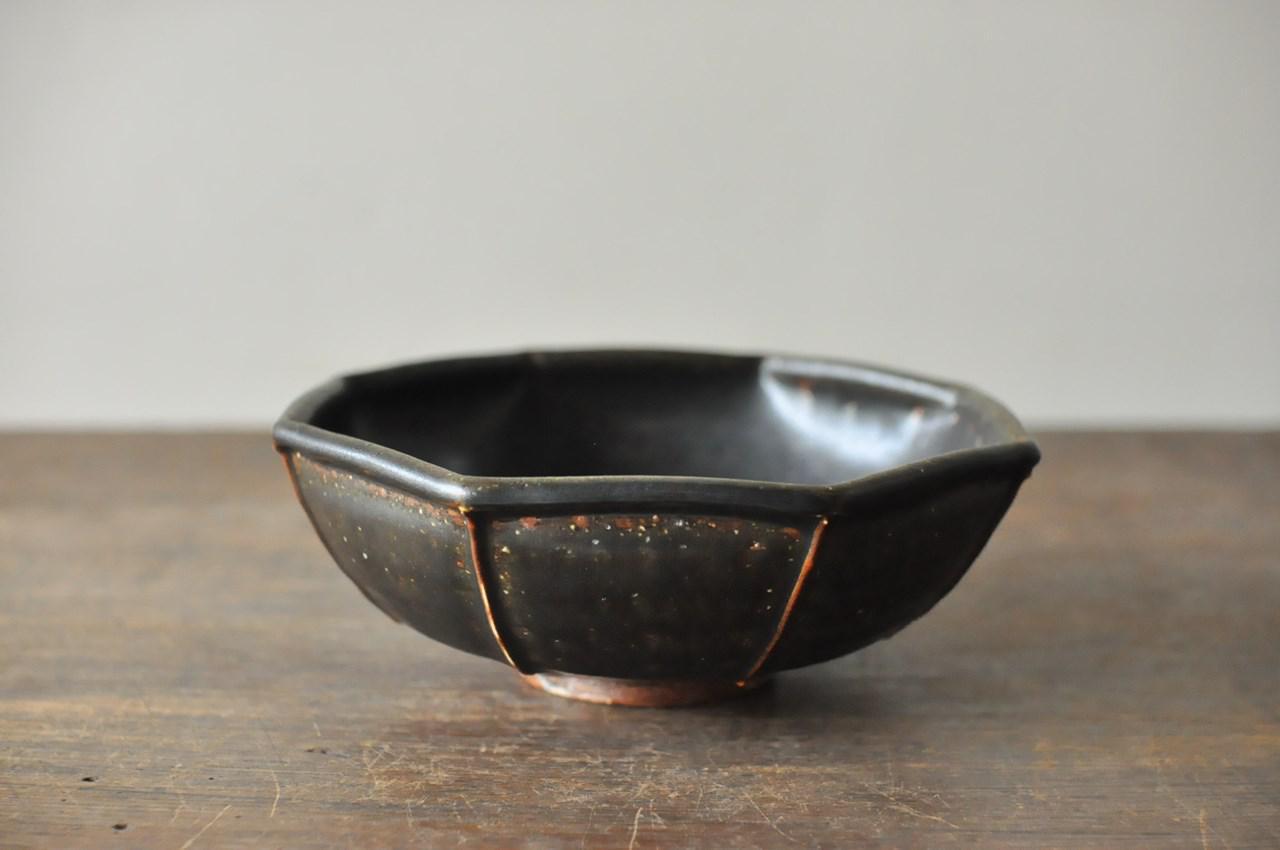 画像: マットな黒が上品な「黒釉八角鉢」。写真の鉢は、小池さん夫妻が10年ほど前から使っていらっしゃる私物で、使うほどにしっとりしてくるのだとか