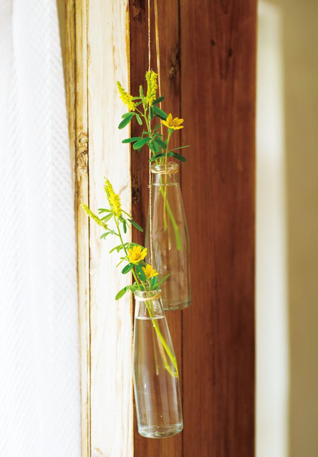 画像: 清涼飲料水の空き瓶を再利用した、手づくりの吊り下げ花瓶。バランスを意識して、アメリカハマグルマとシナガワハギを組み合わせて飾っている