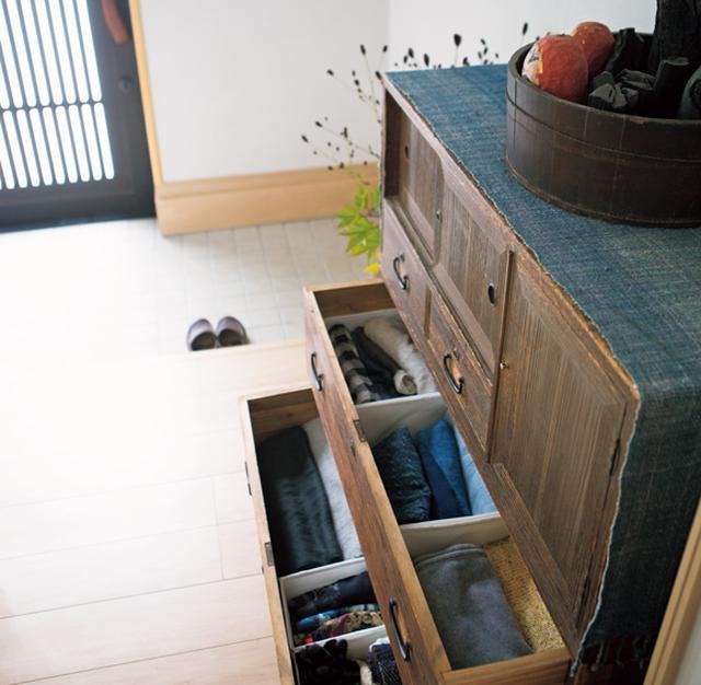 画像: 出かけるときにさっと出せるよう、ストール類は玄関の引き出しに。中を紙箱やブックエンドで区切って