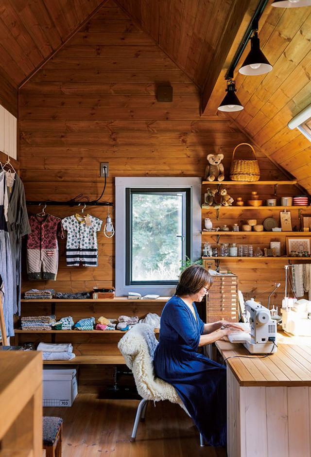 画像: 2階にある祐美さん専用の洋裁スペース。DIYで取り付けたオープン棚に、お手製の服が並んでいます。秘密の屋根裏部屋を思わせる勾配天井はログハウスならでは。まるで子どものころに憧れた童話の1ページのような雰囲気です