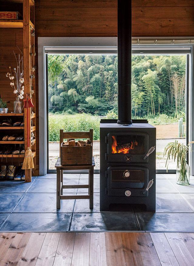画像: 調理も可能な薪ストーブが暮らしの中心。室内からひんぱんに下りる土間は、水ぶきを欠かしません。大きなピクチャーウィンドウからは、奥行きのある里山の風景が広がります