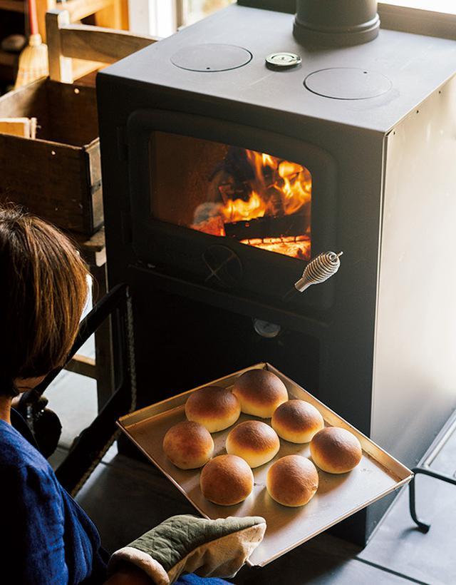 画像: 薪ストーブは、パンを焼きたくてオーブン調理もできるものに。温度や時間など、コツをつかむまでは多少苦労したものの、昨冬はさまざまなパンづくりに挑戦し、何日も続けてピザを焼くこともあったのだとか。焼き上がった丸パンはふっくらもちもち。パンを焼いている間の甘い香りもごちそうです