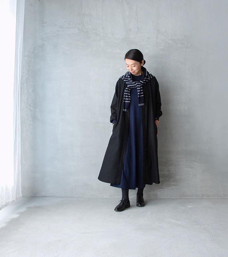 画像: コート、ボーダーのマフラー ネイビーのワンピースに黒のロングコートを羽織って。ボーダー柄のニットをストール代わり巻いてポイントに
