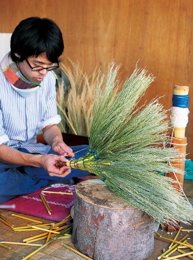 画像: 若手職人のなかでは最古参の吉田慎司さん。美大在学中、中津箒の美しさに魅せられてこの道に入った。京都の箒職人・柳川芳弘さんにも直接指導を受けたそう