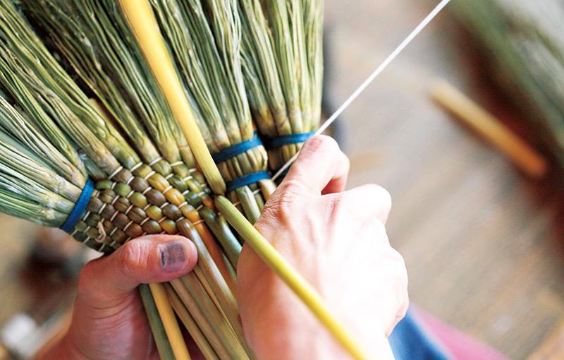 画像: 手箒を編んでいるところ。束ね方、編み方によっても箒の強さやしなやかさは変わってくるそう。どんな色の糸を、どのように使うかは、職人の個性次第