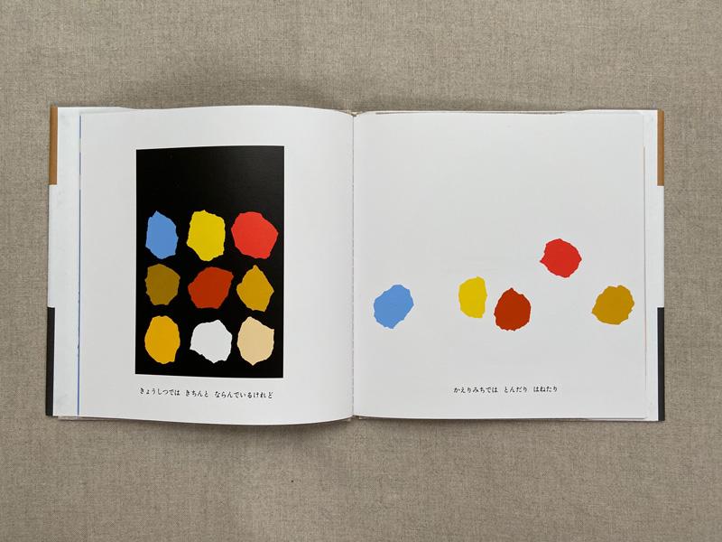 画像: 左ページは教室で並んで座っているあおくんたちの同級生たち。右ページでは飛んだりはねたり。登場人物は、このように色の点で描かれています。