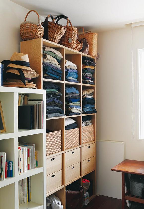 画像: 高さのある棚には、たたんでしまえるニットやパンツ類を収納。棚の上のデッドスペースは、いつの間にか増えていたかごバッグにちょうどいい空間
