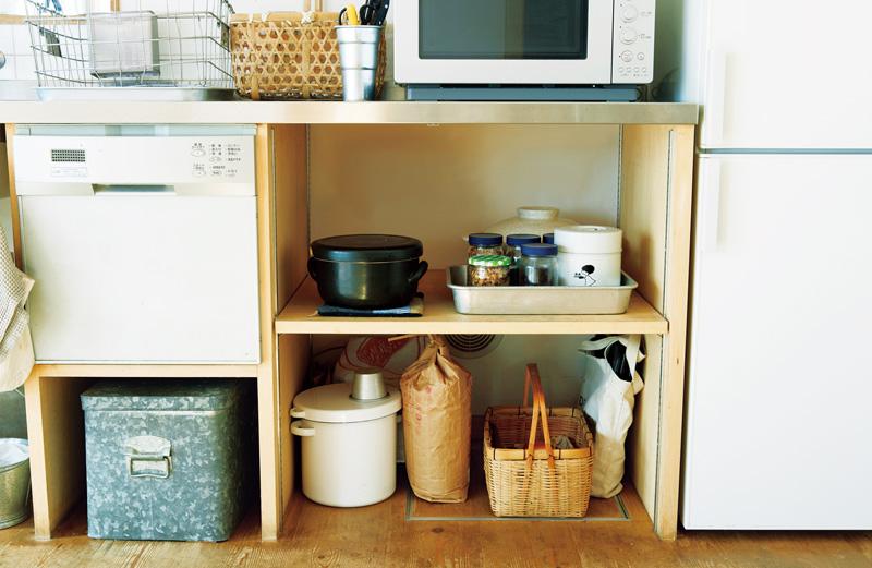 画像: 棚の上段は、炊飯に使う土鍋や朝食用のシリアルなどを。下段は、米やオーブンの天板類が置かれている。ブリキのボックスには、封を開けた食品などを