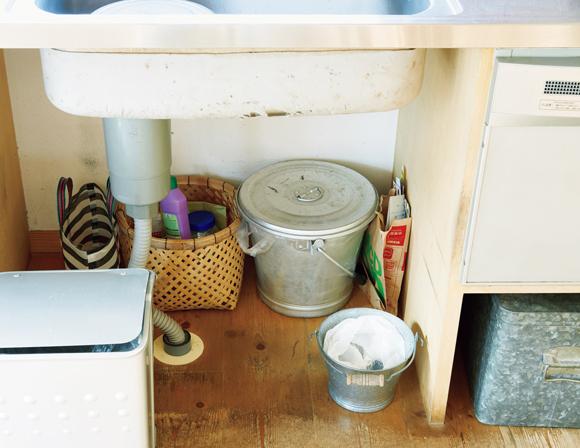 画像: シンクの下は、ごみ箱のスペース。びんや缶などの資源ごみは奥に分別して置いている。そのほか、掃除道具もこの場所に