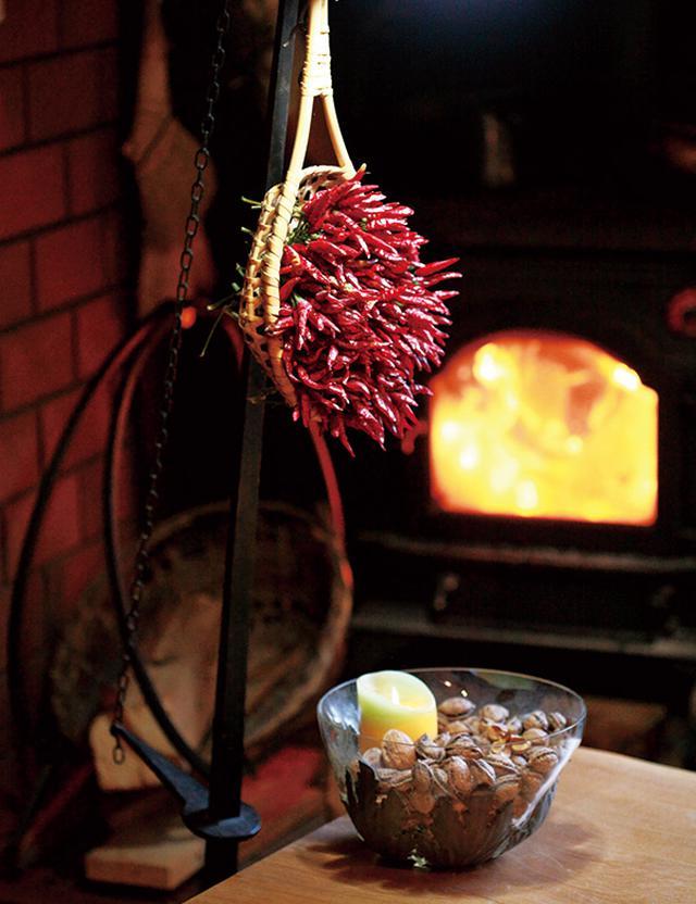 画像: リビングの一角。麺の水切り用ざるには、とうがらし。くるみのボウルにはキャンドルが。個性的な季節のしつらい